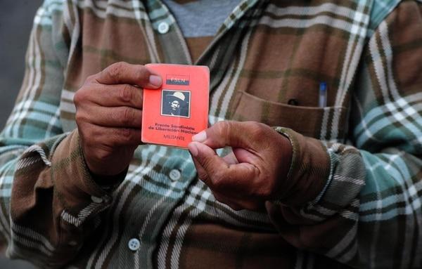 Orlando Gómez sostiene su carnet de militante del FSLN