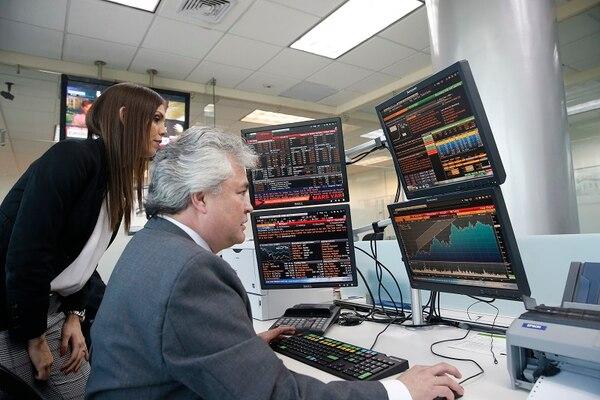 Scotiabank explicó en un comunicado de hecho relevante que mentendrá todos los demás servicios. Aquí Javier Pérez y Mariela Alvarado en las pantallas de negociación de fondo de inversión.