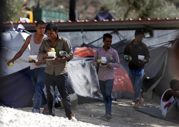 Migrantes cargaban alimentos que recibieron el martes en el campamento de Moria, en la isla griega de Lesbos.