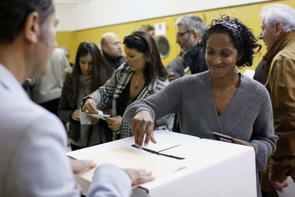 Un mujer deposita su papeleta en el colegio de la Sagrada Familia en Barcelona, durante la jornada participativa, sin carácter vinculante, convocada este domingo para que los catalanes se pronuncien sobre la independencia de Cataluña.