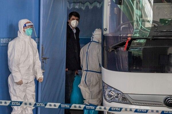 Vladimir G. Dedkov (centro), miembro del equipo investigador de la Organización Mundial de la Salud (OMS), abordó un después de su llegada -este jueves 14 de enero del 2021- al aeropuerto internacional de Wuhan, China. AFP