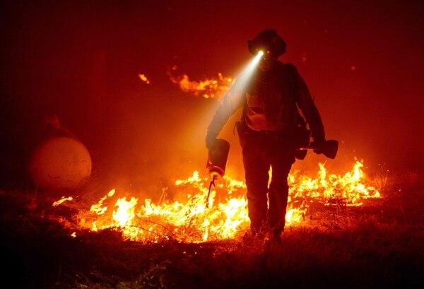 Un bombero camina entre las llamas en el área de Berry Creek, California, el 9 de setiembre del 2020. Foto: AFP