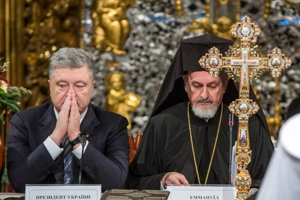 Ukrainian President Petro Poroshenko, left, and Metropolitan Emmanuel attend a closed-door synod of three Ukrainian Orthodox churches to approve the charter for a unified church and to elect leadership in the St. Sophia Cathedral in Kiev, Ukraine, Saturday, Dec. 15, 2018. Poroshenko has told the crowd