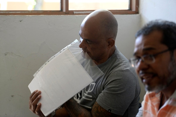 Luis Valentine (izquierda) de 56 años de edad trata de abrir uno de los reconocimientos que obtuvo por su libro de poesía. Junto a él se encuentra Jorge Salas. Fotos de Diana Méndez