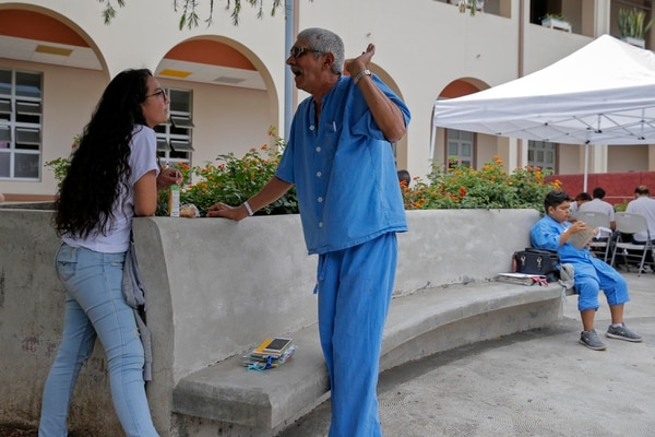 Valentina Suárez, alumna del Liceo de San José, conversa con el paciente Nelson Solís, mientras el paciente Jorman Salazar lee su nuevo libro. Fotos: Mayela López.