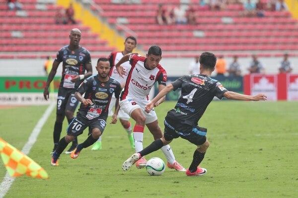 Iván Luquetta maneja la pelota ante la marca de Luis Hernández (4).