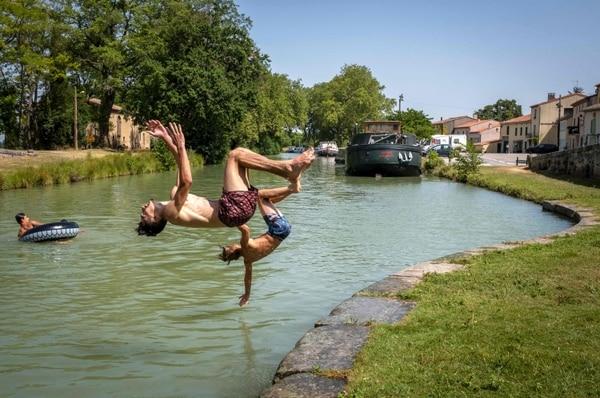 Jóvenes se refrescaban en en Port du Segala, en Labastide d'Anjou, Francia, este martes 23 de julio del 2019.