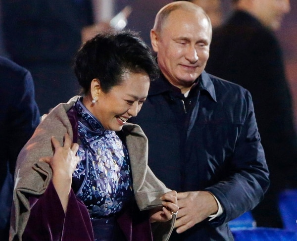 El presidente ruso, Vladimir Putin, coloca un chal sobre los hombros de Pen Liyuan, esposa del presidente chino Xi Jinping durante una cena de gala en la cumbre Apec.
