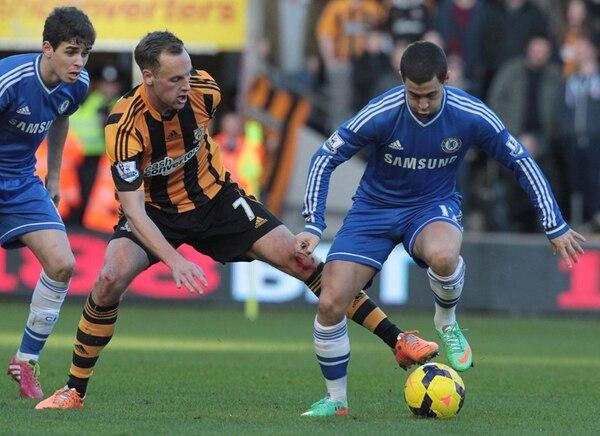 El volante irlandés del Hull, David Meyler (i.), disputa el balón con el mediocampista belga del Chelsea, Eden Hazard, quien ayer marcó el primero. | AFP