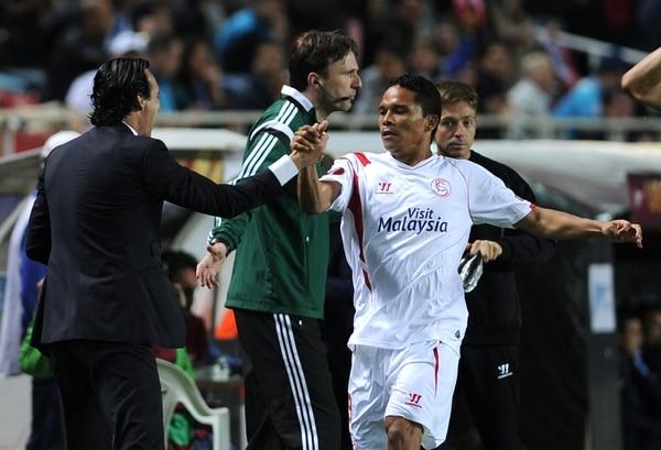 Carlos Bacca (izq.) celebra su anotación con el técnico del Sevilla, Unai Emery.