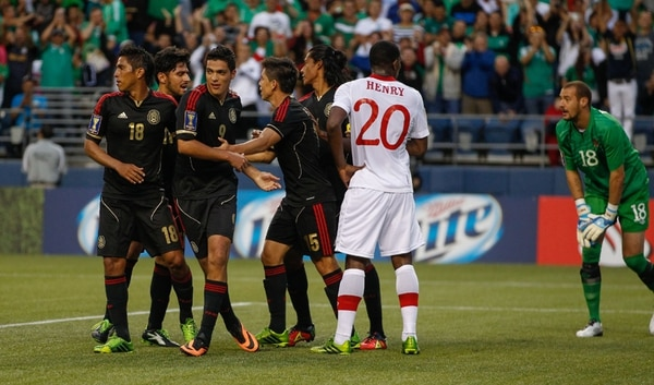 Raúl Alonso Jíménez (9) abrió la senda del triunfo para la selección de México, con un gol logrado en jugada de tiro de esquina. El canadiense Doneil Henry (20) queda sin consuelo ante la felicidad de los jugadores rivales.   AFP