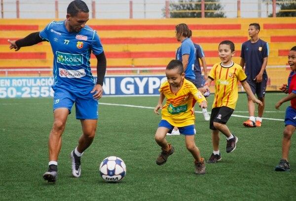 José Leitón juega con un niño en la cancha del Rosabal Cordero.