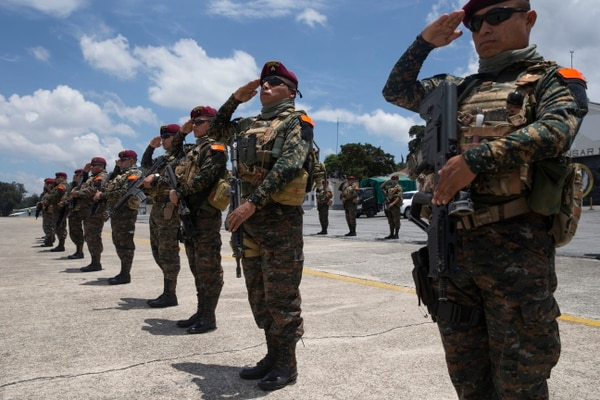 Un grupo de soldados saludan cuando los restos de tres camaradas que fueron asesinados en enfrentamientos con presuntos narcotraficantes llegan a una base de la fuerza aérea en la ciudad de Guatemala, el jueves 5 de septiembre de 2019. . (AP Photo/Moises Castillo)