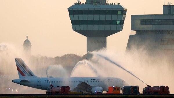 Bomberos este domingo por la tarde en Berlín rociaron agua sobre un avión de Air France con destino a París como parte de la ceremonia de clausura de operaciones aéreas en el aeropuerto Berlin 'Otto Lilienthal' Tegel. Fotografía: AFP.