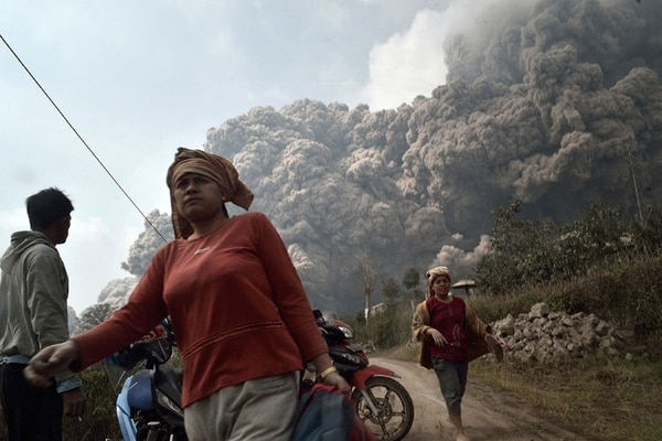 La gente huye de la erupción de ceniza del Monte Sinabung que se acerca a poblaciones vecinas. | AFP