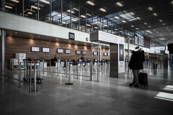 A man waits in front of counters at the deserted international airport of Orly, on March 30, 2020, a day before its closure due to a drop in traffic amid the spread of the COVID-19 infection, caused by the novel coronavirus. (Photo by Philippe LOPEZ / AFP)