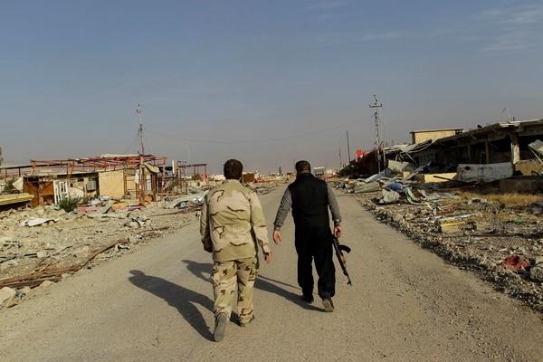 Ali Hussein (der.) y su hijo avanzan hacia el que era su hogar para ver qué quedó de su negocio de carros usados en Bashiqa. El pueblo, que estaba en poder del Estado Islámico, fue saqueado por los yihadistas y destruido por los posteriores combates.entre el grupo terrorista y las fuerzas iraquíes.