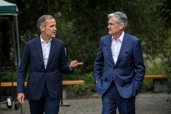 Bank of England Governor Mark Carney, left, and Jerome Powell, Chairman of the Board of Governors of the Federal Reserve System, right, chat after Powell's speech at the Jackson Hole Economic Policy Symposium on Friday, Aug. 23, 2019, in Jackson Hole, Wyo. (AP Photo/Amber Baesler)