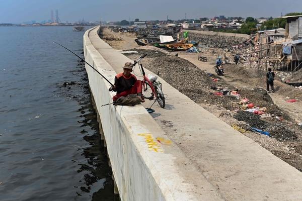 El pasado 4 de julio un hombre pescaba desde lo alto de un gigantesco malecón en el norte de Yakarta. (BAY ISMOYO / AFP)