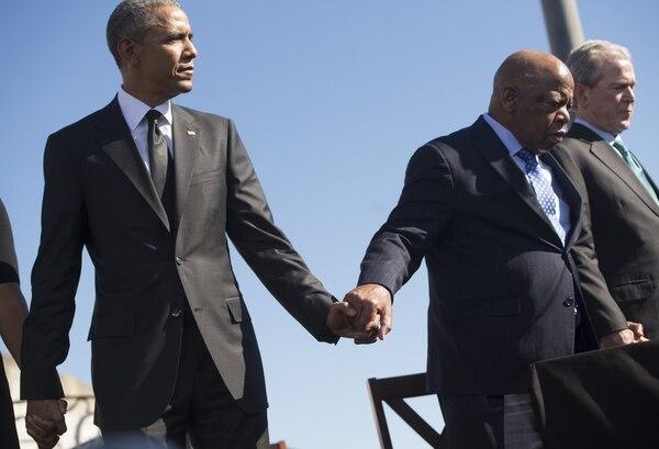 El presidente de los Estados Unidos, Barack Obama, sosteniendo la mano del representativo John Lewis en la conmemoración del 50 aniversario de la marcha pacífica por el derecho al sufragio de los afroamericanos.