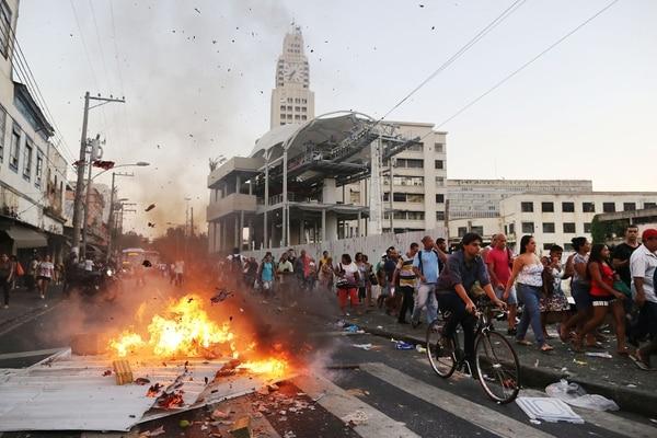 Personas pasan junto a una barricada ardiendo durante manifestantes por el alza en las tarifas de autobuses, frente a una estación de tren en Río de Janeiro.