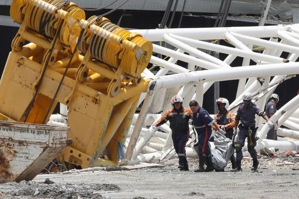 Rescatistas recuperan uno de los cuerpos de los obreros fallecidos. | AP