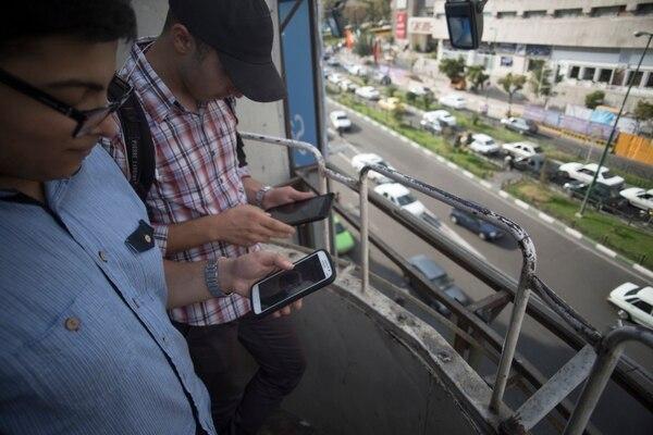 Dos hombres buscan señal 3G en el balcón de un edificio en Teherán. Irán está relajando el control sobre el uso de Internet.