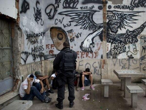 Un oficial custodia a un grupo de detenidos durante la ocupación.   AFP.
