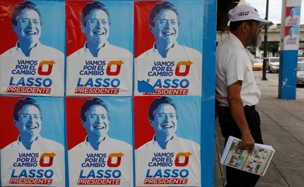 Un hombre se apoya en un muro cubierto con propaganda del candidato presidencial Guillermo Lasso en Guayaquil, Ecuador.
