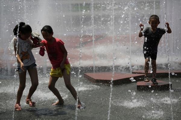En la imagen tres niños se refrescan en un parque en la ciudad de Shanghai, China.