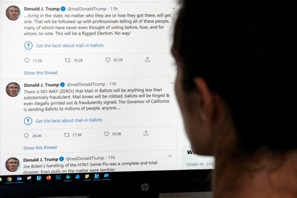 This illustration photo shows an editor in Los Angeles looking at the official Twitter account of US President Donald Trump on May 26, 2020, with two tweets by the president under which Twitter posted a link reading