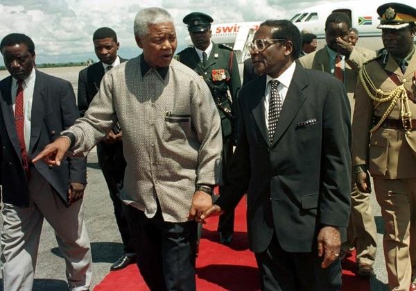 El expresidente sudafricano Nelson Mandela (izquierda) junto a Robert Mugabe en Harare, en diciembre de 1998.