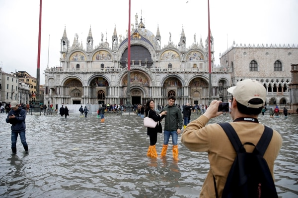Turistas posan para fotos en la Plaza de San Marcos inundada en Venecia, Italia, el 1°. de noviembre del 2018. Foto con fines ilustrativos: AP