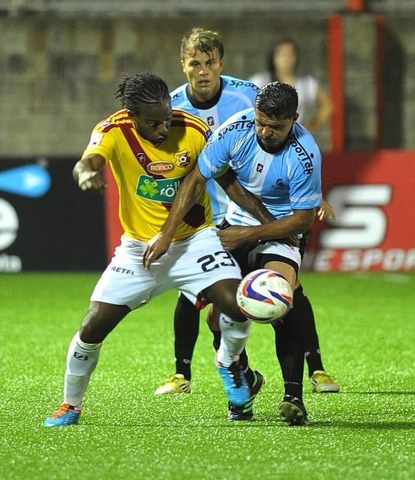 El florense Víctor Núñez (23) fue marcado el sábado pasado por los universitarios Mauricio Montero y Andrés Núñez (atrás).   MANUEL VEGA