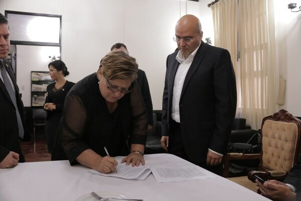 Laura Garro, jefa de fracción del PAC, firmó de primera el documento que sella un convenio entre Acción Ciudadana y el Frente Amplio para constituirse como 'Bloque Progresista'. Supervisa la firma, el jefe de fracción del FA, Edgardo Araya. | CORTESÍA DEL FRENTE AMPLIO.