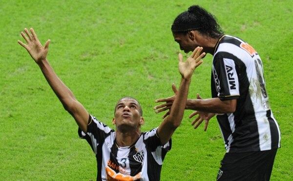 Leonardo Silva (izquierda), del Atlético Mineiro, celebra el gol del empate en el marcador global, ante el Olimpia. Lo acompaña Ronaldinho.   AFP