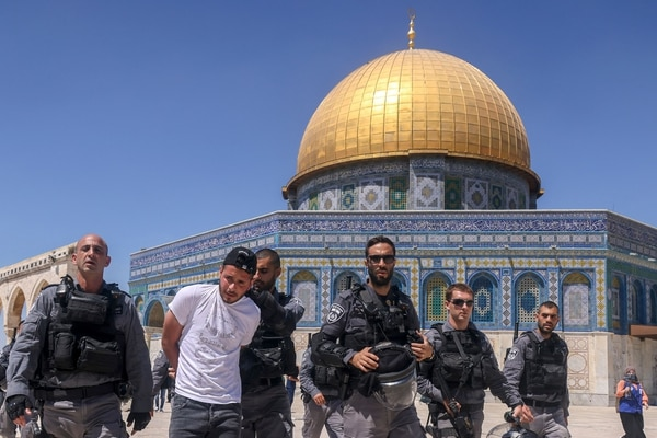 Members of the Israeli security forces detain a Palestinian man in front of the Dome of the Rock mosque following Friday prayers in Jerusalem's Al-Aqsa mosque complex, on June 18, 2021, as Palestinians protested in response to chants by Israeli ultranationalists targeting Islam's Prophet Mohammed in the March of Flags earlier this week. (Photo by AHMAD GHARABLI / AFP)