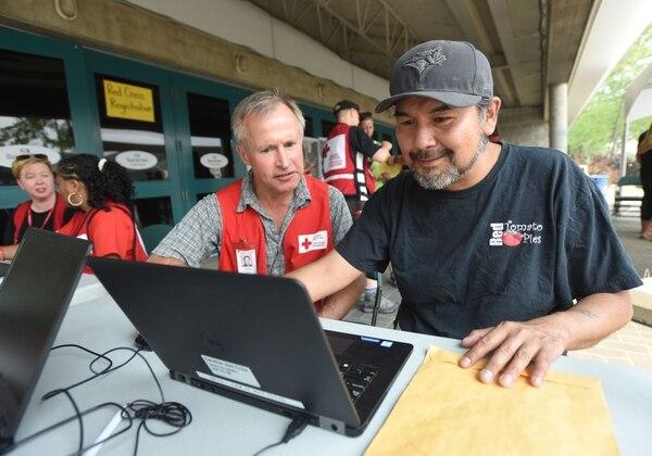 El voluntario de la Cruz Roja Canadiense, Nicholas Albright, asiste a Frank David con el registro de ayuda,luego de ser evacuado de su casa debido a un incendio forestal.
