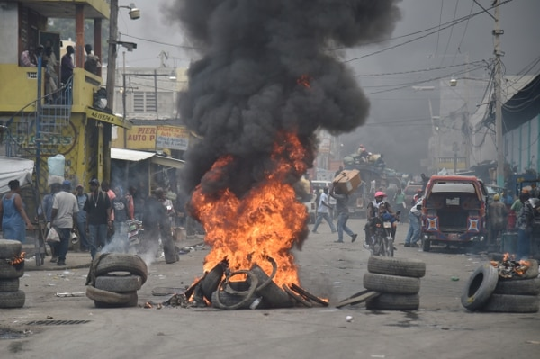 Varias personas caminan en medio de llantas quemadas en el centro de Puerto Príncipe, durante una serie de protestas callejeras.
