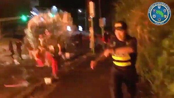 El hombre con pantalón rojo lanza combustible a un oficial de la Fuerza Pública. Captura de video: MSP