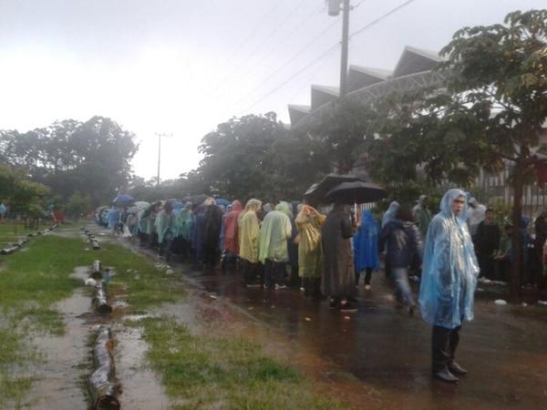 En las afueras del Estadio Nacional y bajo la lluvia, los seguidores de Black Sabbath esperan