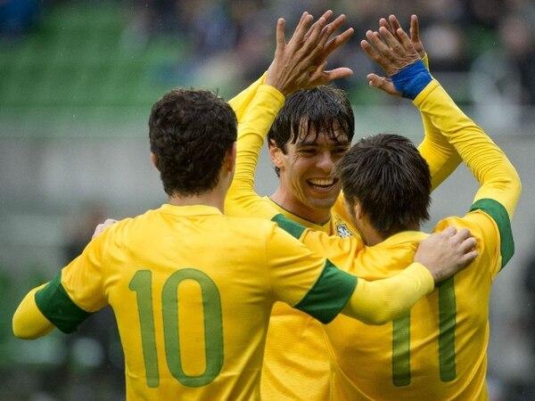 El jugador Kaka celebra con Neymar y Oscar la anotación desde el punto de penal hoy contra Japón. | AFP.
