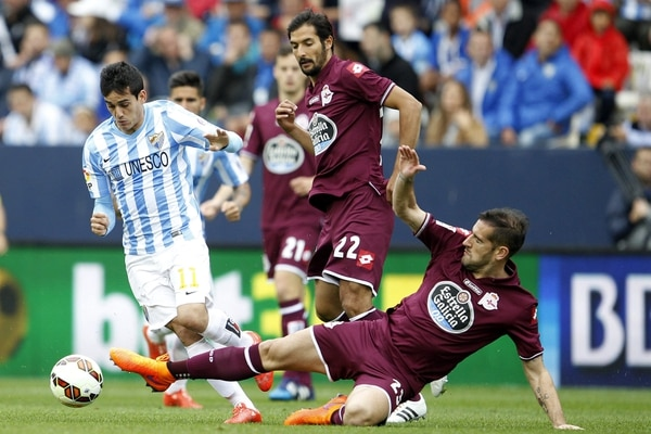 El volante costarricense del Deportivo La Coruña, Celso Borges, intenta arrebatar el balón al delantero del Málaga Juanmi (izq.).