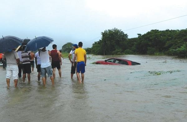 Un grupo de damnificados observa un vehículo afectado por el desbordamiento del río Guamol, en el istmo de Tehuantepec.   EFE