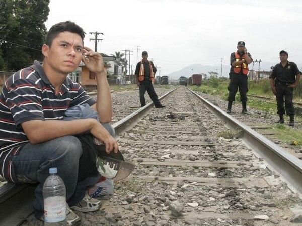 Un migrante no identificado es vigilado por policías mientras espera el paso del tren sobre las vías ferreas del tramo Veracruz-Oaxaca. Foto: Archivo