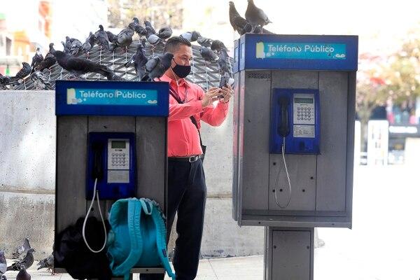 Ante la ausencia de usuarios, algunos vendedores ambulantes en San José aprovechan los teléfonos públicos como casilleros. Foto: Rafael Pacheco.