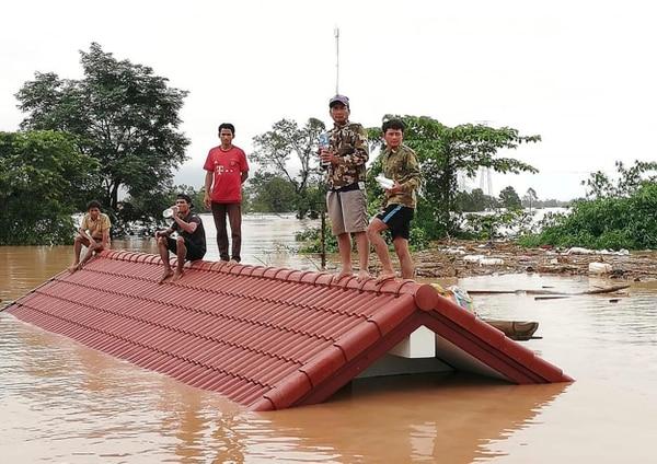 Estos aldeanos tuvieron que subir al techo de una vivienda para sobrevivir a la inundación causada por la ruptura de una presa en el sureste de Laos.