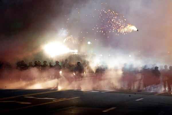 Las fuerzas policiales lanzaron una bomba, el miércoles en la noche, mientras se enfrentaban contra manifestantes en las calles de la ciudad de Ferguson, Misuri. | AP