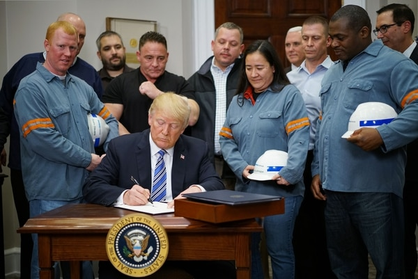 El presidente de Estados Unidos, Donald Trump, firmó la imposición de aranceles al acero y el aluminio en la Oficina Oval de la Casa Blanca. Se hizo acompañar por trabajadores dela industria siderúrgica. Foto AFP/MANDEL NGAN