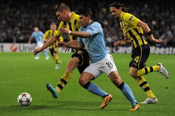 El delantero argentino Sergio Aguero del Manchester City, disputa el balón frente a Lukasz Piszczek y Neven Subotic del Borussia Dortmund.   AFP
